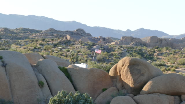 joshua tree national park, zoom out from a joshua tree stone age rock formations, two people in the far background, - joshua tree national park stock videos & royalty-free footage