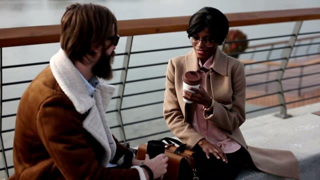 Journalist and cameraman taking a coffee break