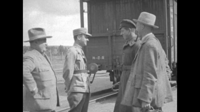journalist arthur ransome smoking a pipe and pathe cameraman george ercole with a cigar; they talk with two uniformed men and walk past a line of... - 撮影機材点の映像素材/bロール