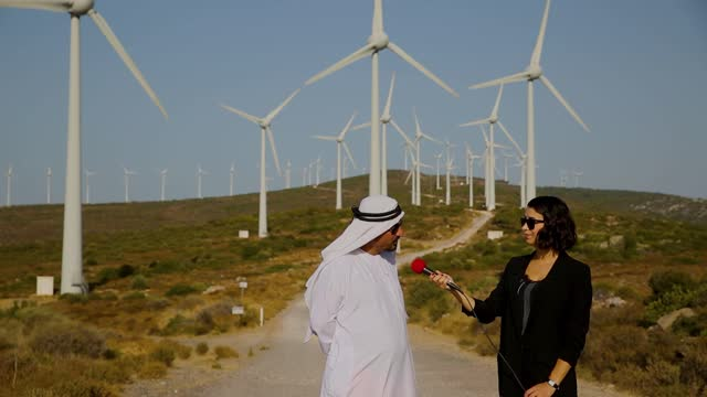 journalist conducting interview of arab businessman about renewable energy in wind turbine. journalism industry, live streaming concept. - middle east stock videos & royalty-free footage