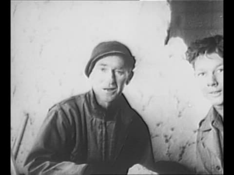 vídeos de stock, filmes e b-roll de journalist ernie pyle sits on floor in room while us soldier in next room looks toward pyle through huge hole in wall during world war ii / pyle sits... - autografando