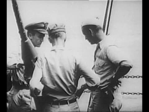 stockvideo's en b-roll-footage met journalist ernie pyle sits on log as he eats with a us soldier during world war ii / montage rear shots pyle and officers look over side of ship;... - plantdeel