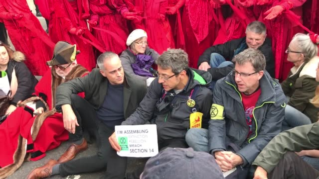 vídeos de stock e filmes b-roll de journalist george monbiot joins fellow extinction rebellion protesters by laying down and obstructing the street the action is a direct challenge to... - protestante