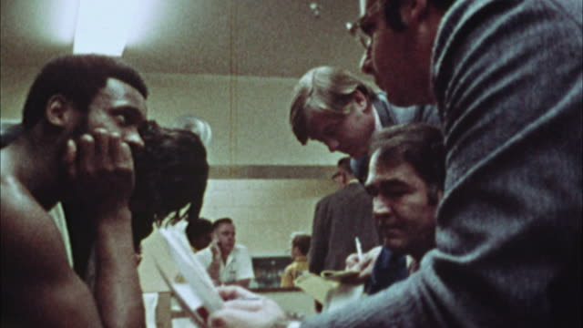 vidéos et rushes de cu, composite, journalist interviewing basketball players and coach after match,1970's, los angeles, california, usa - journalist