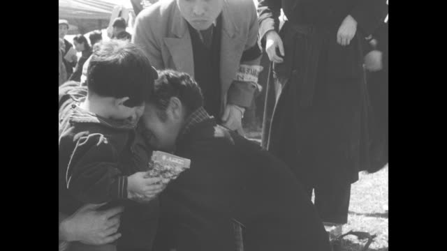 vídeos de stock, filmes e b-roll de journalist talks to repatriated japanese woman as she arrives in maizuru home from china / repatriates approach as they walk in single file through... - emigração e imigração
