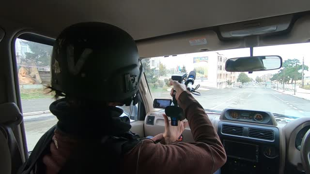 vidéos et rushes de journalist wearing helmet and protective flak jacket filming as he rides a car through empty streets during azerbaijani shelling on november 05, 2020... - caméraman