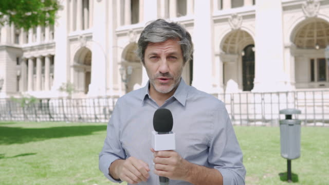 journalist with microphone on the city streets - tv reporter stock videos & royalty-free footage