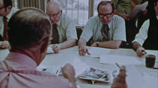 vidéos et rushes de ms, pan, journalists having meeting, 1970's, los angeles, california, usa - journalist