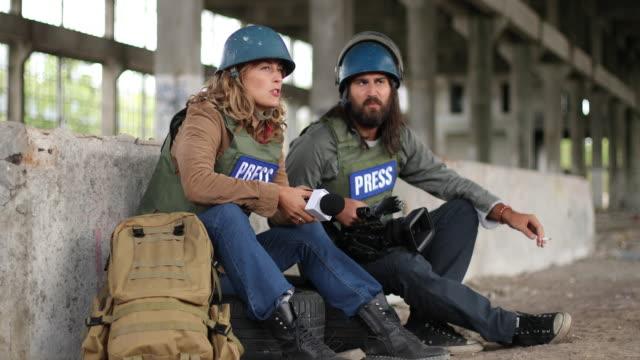vidéos et rushes de journalistes dans la zone de guerre se reposant - équipement photographique