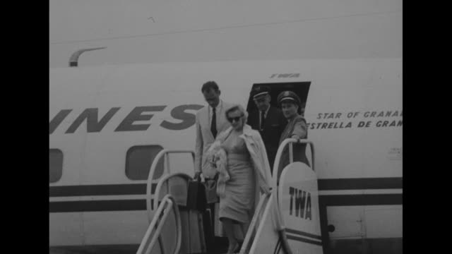 journalists wait at airport, photographers stand on cars with cameras / marilyn monroe wearing sunglasses and arthur miller deplane from twa plane /... - ローレンス オリビエ点の映像素材/bロール
