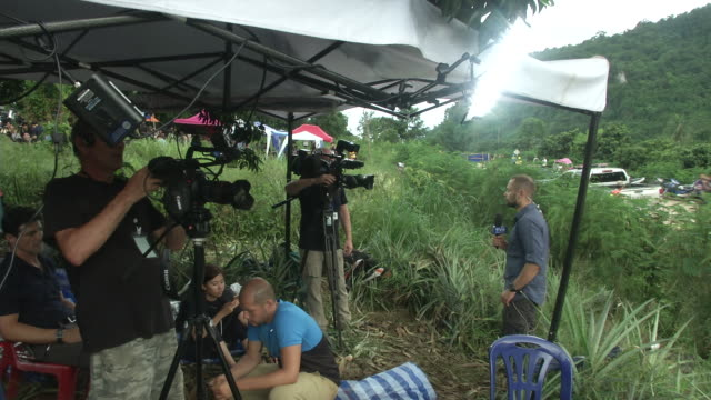 journalists working at the tham luang cave area with 12th and 13th persons after divers evacuated some of the boys among a group of 13 trapped in a... - chiang rai province stock videos and b-roll footage