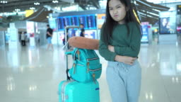 Journey of Asian little girl at the airport, waiting for her flight ,facial expression , stomachache , suffering from cystitis, touching abdomen and feeling pain