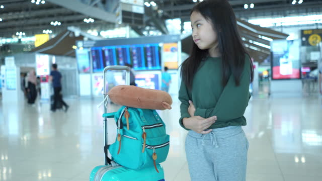 journey of asian little girl at the airport, waiting for her flight ,facial expression , stomachache , suffering from cystitis, touching abdomen and feeling pain - urinary system stock videos & royalty-free footage