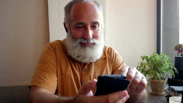Joyful and smiling softly bearded man using his phone