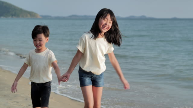 joyful asian boy and girl with fun along edge of sunset sea surf on sand beach.children, happy family holidays, family, lifestyle, friendship, people, relationship, vacations - sister stock videos & royalty-free footage