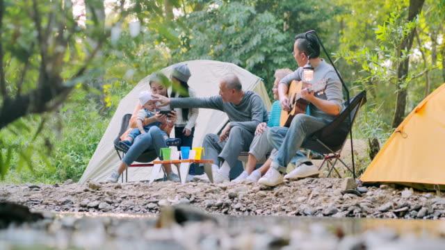 joyful asiatiska stor familj njuter i camping. familj, livsstil, människor, flera generationer, äldre, semester, förhållande, semester, pensionering, hälsosam vård och medicin koncept. sydostasien och östasien: generationsfamilj - east asian ethnicity bildbanksvideor och videomaterial från bakom kulisserna