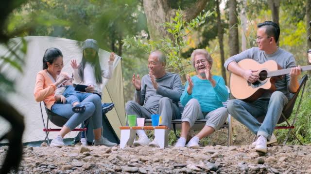 fröhliche asiatische große familie genießen auf dem campingplatz. familie,lifestyle,menschen,mehrgenerationen,ältere,urlaub,beziehung,urlaub,ruhestand,gesundepflege und medizin konzept. südostasien und ostasien: generationenfamilie - east asian ethnicity stock-videos und b-roll-filmmaterial