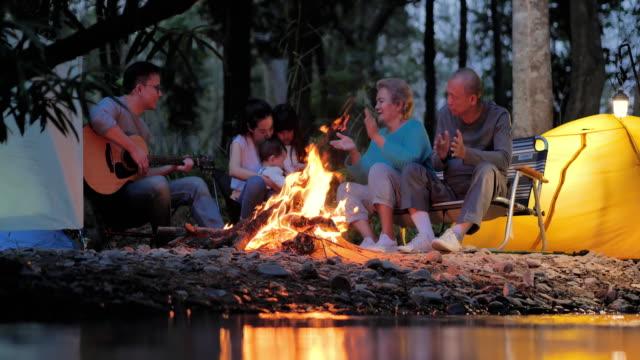fröhliche asiatische große familie genießen in camping in der nacht in der nähe von lagerfeuer auf wald. familie,lifestyle,menschen,mehrgenerationen,ältere,urlaub,beziehung,urlaub,ruhestand,gesundepflege und medizin konzept. südostasien und ostasien: - east asian ethnicity stock-videos und b-roll-filmmaterial