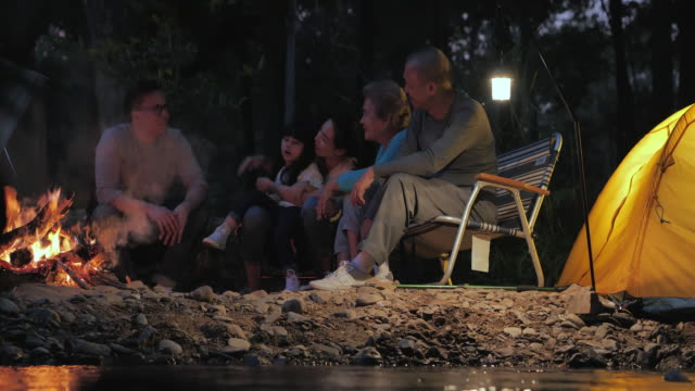 joyful asian large family enjoying in camping at night near campfire on forest.family,lifestyle,people,multi-generation,elderly,vacations,relationship,holiday,retirement,healthycare and medicine concept.south east and east asia: generational family - east asian ethnicity video stock e b–roll