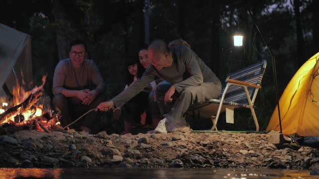 joyful asian large family enjoying in camping at night near campfire on forest.family,lifestyle,people,elderly,vacations,relationship,holiday,retirement,healthycare and medicine concept.south east and east asia: generational family,bonfire - camping stock videos & royalty-free footage