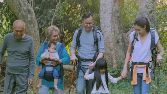 fröhliche asiatische große familie zu fuß im camping während der vermittlung von kindern über nachhaltigkeit auf wald. glückliche familie verbringen zeit zusammen im freien. kinder über nachhaltigkeit unterrichten - east asian ethnicity stock-videos und b-roll-filmmaterial