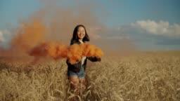 Joyful asian woman with colored smoke bomb outdoors