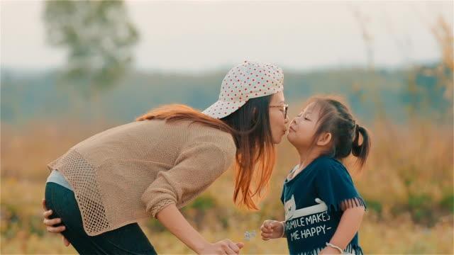 fröhliche asiatische junge mutter küsst ihr kind in wange mit dem verschwommenen feld zusammen - zungenkuss stock-videos und b-roll-filmmaterial