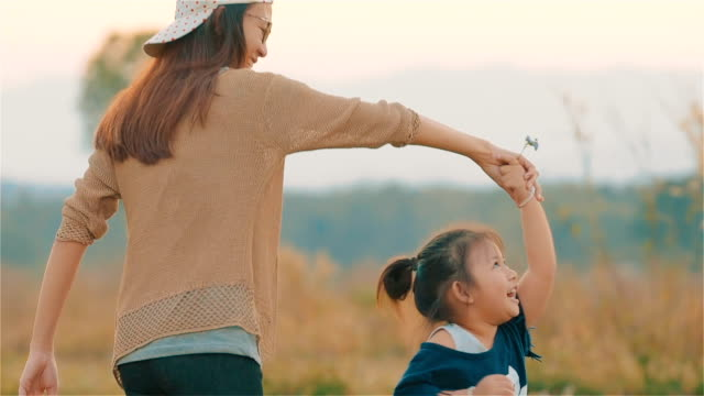 Joyful Asian young mother with daughter playing in the blurred field together