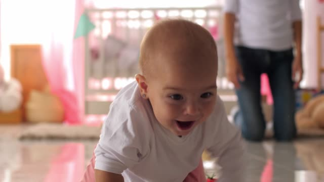 joyful baby girl looking at camera while crawling around her nursery - crawling stock videos & royalty-free footage