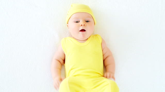 joyful baby in yellow smiling and playing