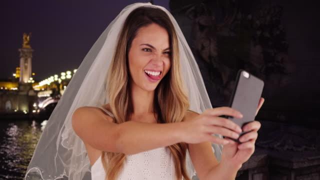 vidéos et rushes de joyful bride taking fun selfies in paris at night - couple marié