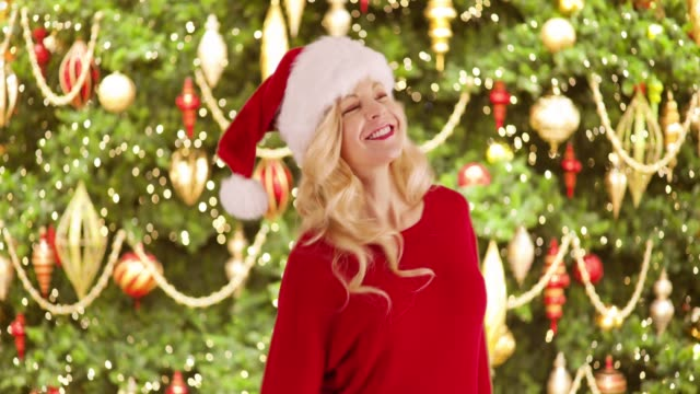 joyful caucasian woman in red sweater dancing in front of christmas tree smiling - santa hat stock videos & royalty-free footage