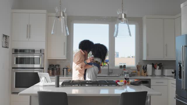vídeos de stock e filmes b-roll de joyful couple dances in their kitchen while preparing food - on the move
