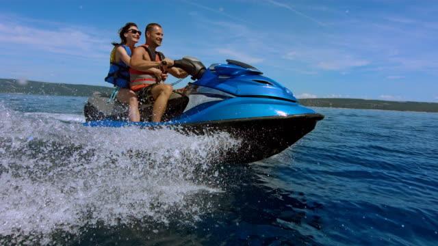 slo mo allegra coppia equitazione una moto d'acqua - acquascooter video stock e b–roll