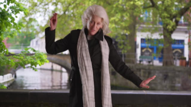 joyful dancing senior woman on vacation having fun in bruges - carefree stock videos & royalty-free footage