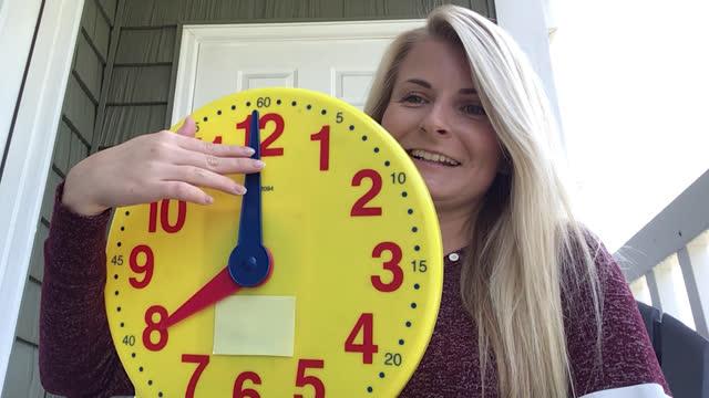 vidéos et rushes de joyful elementary school teacher demonstrating how a clock works to her students over zoom - montrer