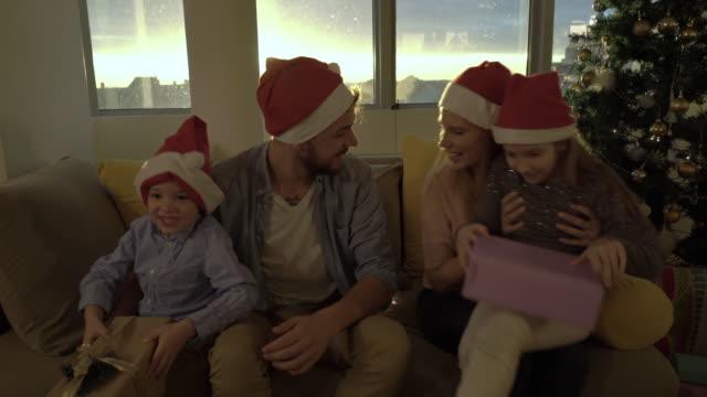 Joyful family enjoying in Christmas presents and having fun at home.