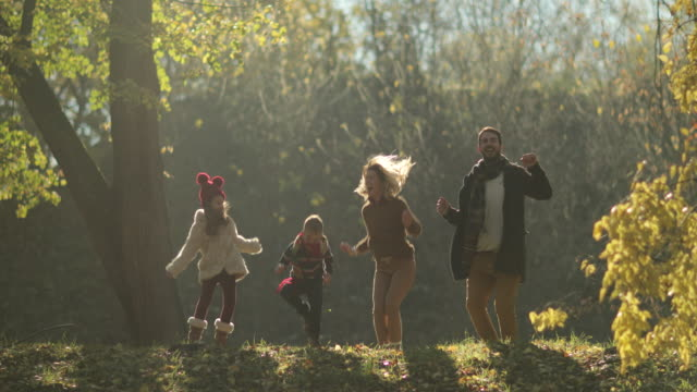 vídeos de stock e filmes b-roll de joyful family jumping in the park and having fun in autumn. - filho