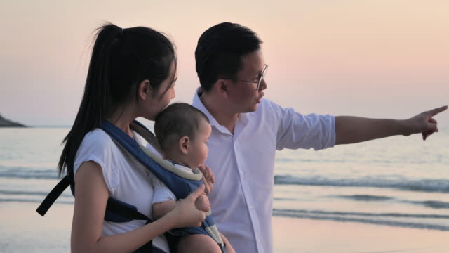 joyful father, mother, baby son walk with fun along edge of sunset sea surf on sand beach. active parents and people outdoor activity on summer vacations with children.happy family holidays.family,lifestyle,people,life insurance,vacations - istock - east asian ethnicity video stock e b–roll
