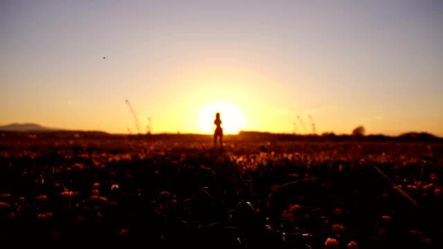 SLO MO Joyful girl in the meadow at sunset