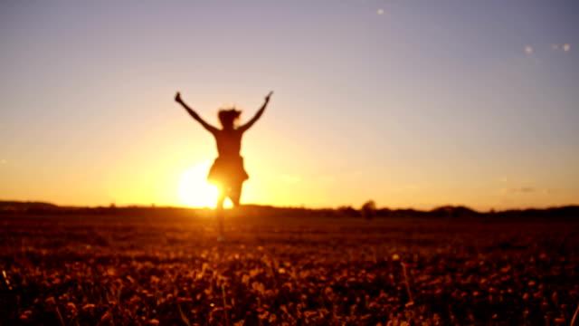 slo mo gioiosa ragazza corre in erba al tramonto - zona erbosa video stock e b–roll