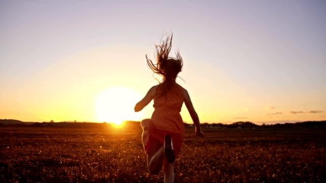 SLO, MO, fröhliche Mädchen läuft auf Gras im Sonnenuntergang