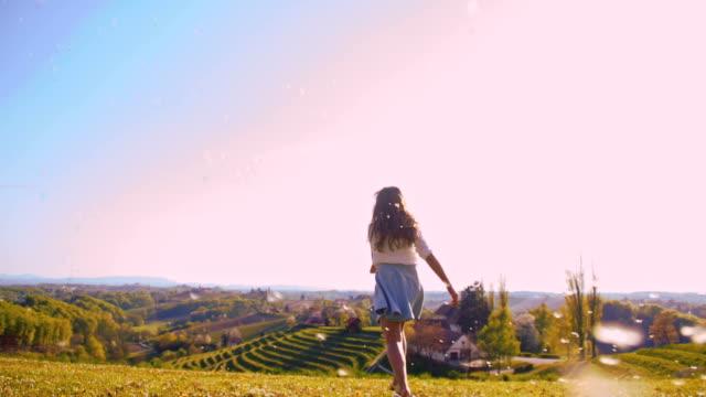 SLO MO Joyful girl running with dandelion seeds