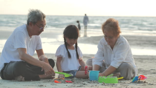 joyful grandfather, grandmother and granddaughter playing toys for kids in sandbox on the beach.family,lifestyle,people,elderly,life insurance,vacations,relationship,holiday,children,retirement,healthy care concept. - chinese ethnicity stock videos & royalty-free footage