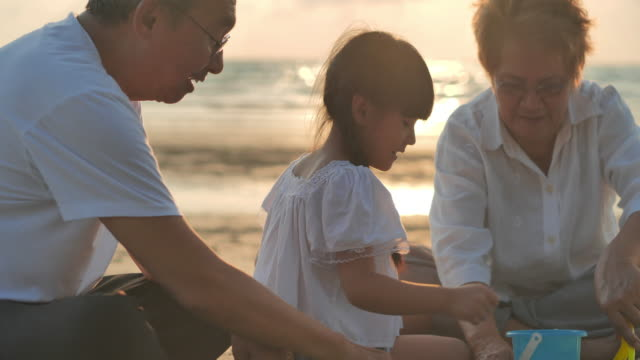 joyful grandfather,grandmother and granddaughter playing toys for kids in sandbox on the beach.family,children,lifestyle,people,elderly,life insurance,vacations,relationship,holiday,retirement,healthy care concept. - grandchild stock videos & royalty-free footage