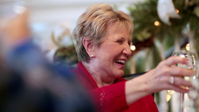 joyful grandmother raises glass to toast and clink with family at dinner table - christmas stock videos & royalty-free footage