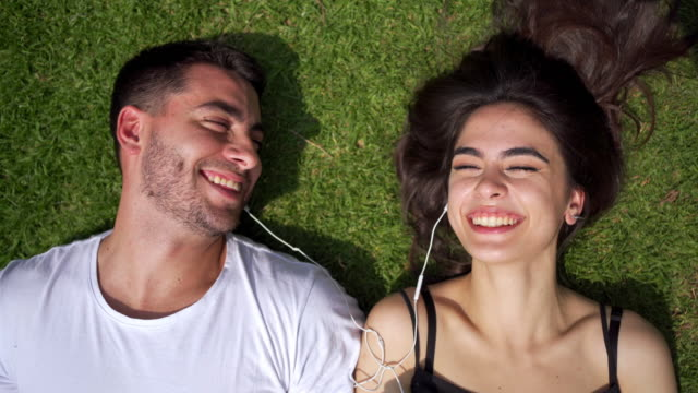 joyful hispanic couple in bliss while resting on grass - falling in love stock videos & royalty-free footage