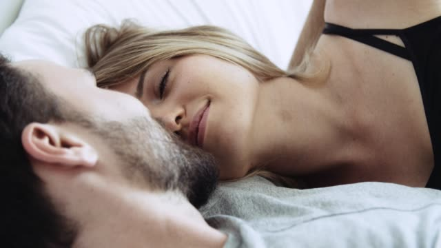 joyful man and woman kissing and relaxing in bed - sex woman bed stock videos & royalty-free footage