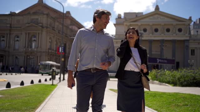 fröhlicher mann und frau, die eine straße hinuntergehen, während sie sprechen - verlieben stock-videos und b-roll-filmmaterial
