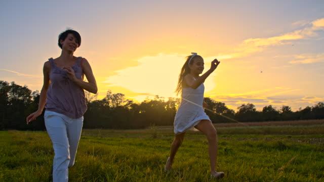 TS Alegre mãe e filha a correr ao pôr do sol